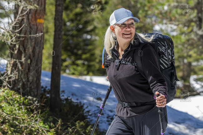 Mature woman hiking by trees on Munkel Trail in Val di Funes, Italy