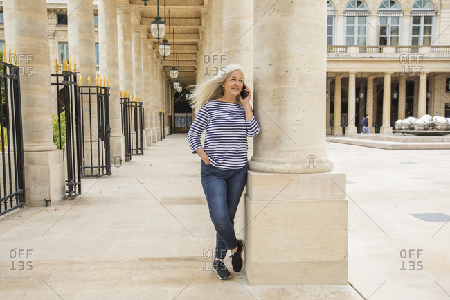 Woman on phone by columns of Palais-Royal in Paris, France