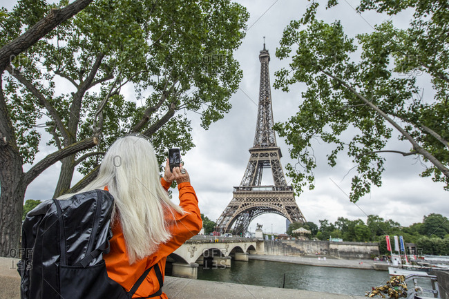 Woman photographing Eiffel Tower with smart phone in Paris, France