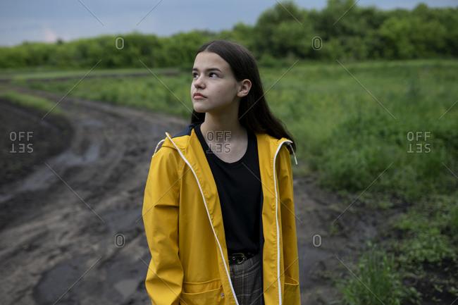 Teenage girl wearing yellow raincoat on country road