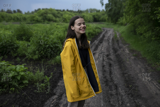 Smiling teenage girl wearing yellow raincoat on country road
