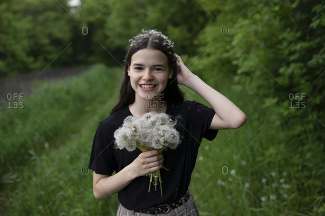 Smiling teenage girl holding dandelions in a field