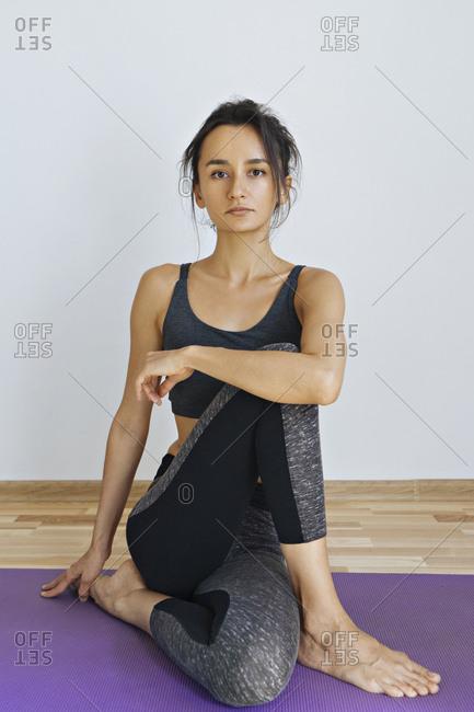 Woman wearing sportswear sitting on yoga mat
