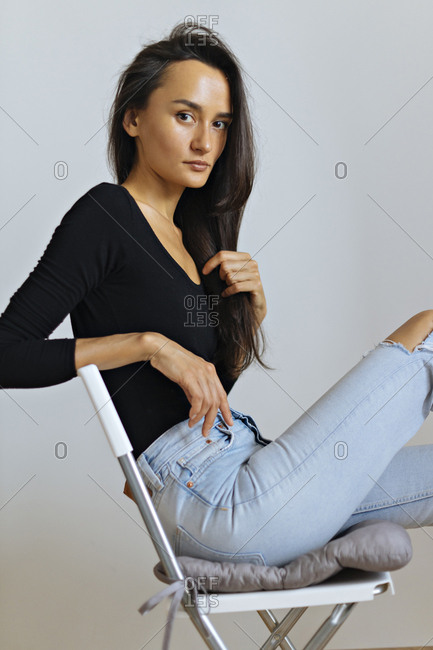 Woman wearing black top and ripped jeans on chair