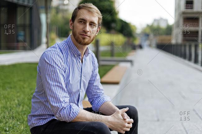 Man wearing striped shirt sitting on bench
