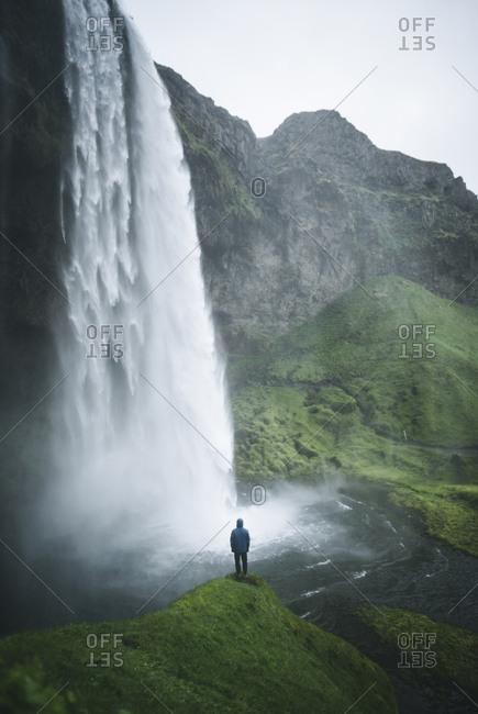 Man standing by Seljalandsfoss waterfall in Iceland