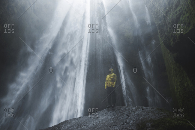 Man wearing yellow raincoat by Seljalandsfoss waterfall in Iceland