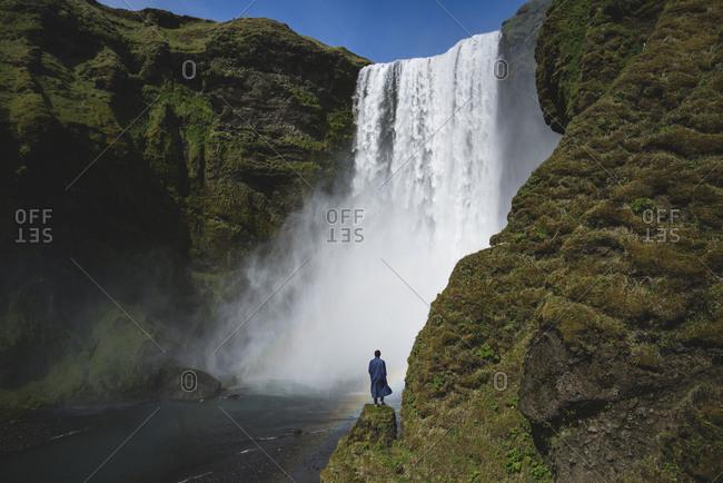 Man standing by Skogafoss waterfall in Iceland