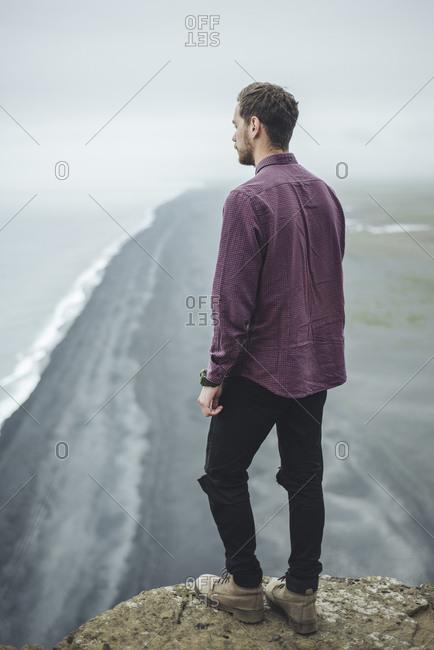 Man wearing purple shirt above beach in Vik, Iceland