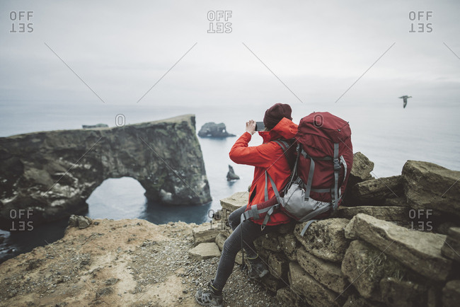 Female hiker photographing natural arch in Vik, Iceland