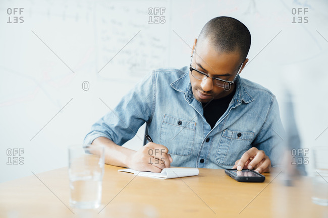 Man using smart phone while writing on note pad