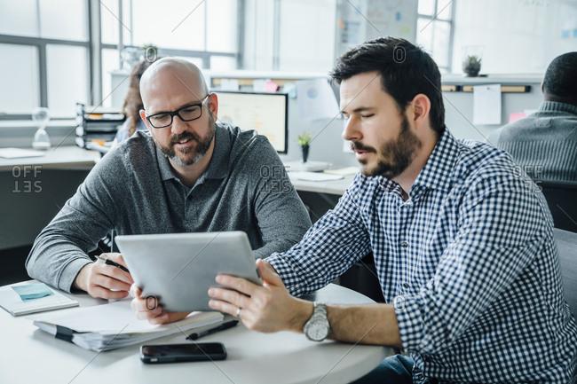 Men using digital tablet during meeting in office