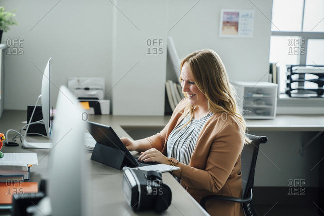 Smiling woman using digital tablet in office