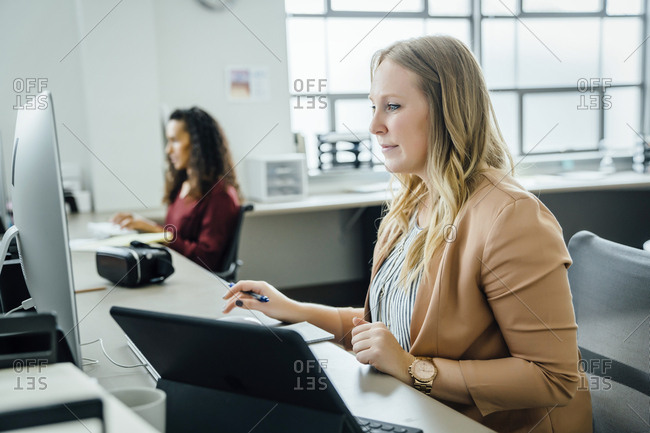 Woman using computer and digital tablet in office