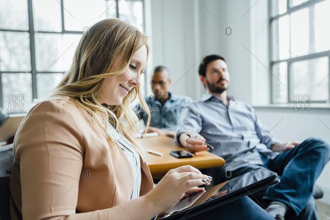 Woman using digital tablet during meeting