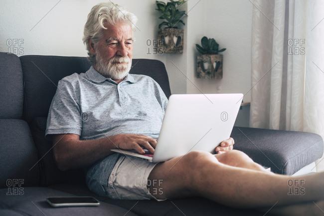 Senior man using laptop on sofa