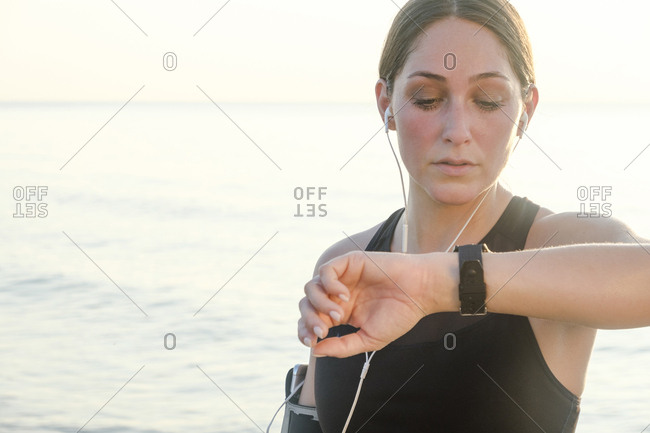 Woman wearing headphones checking wrist watch on beach