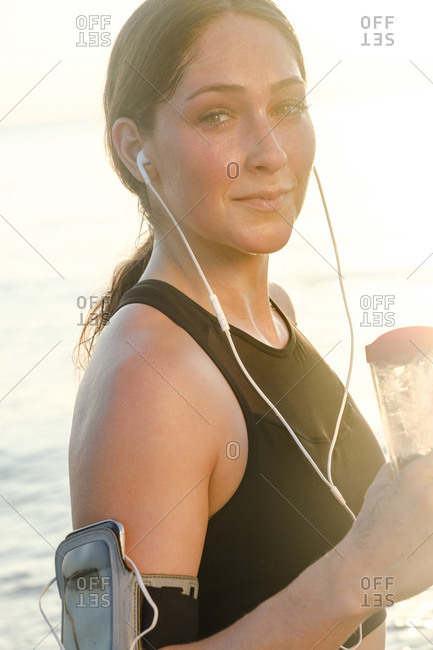 Woman wearing headphones holding water bottle