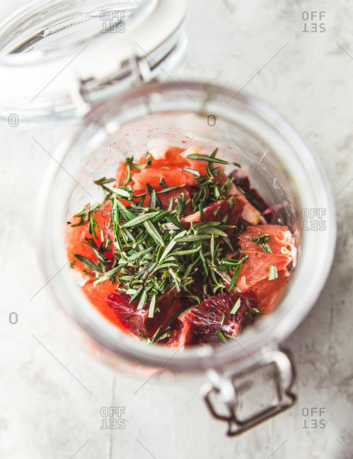 flip top jar filled halfway full with chopped ingredients to make citrus, bood orange, rosemary shrub