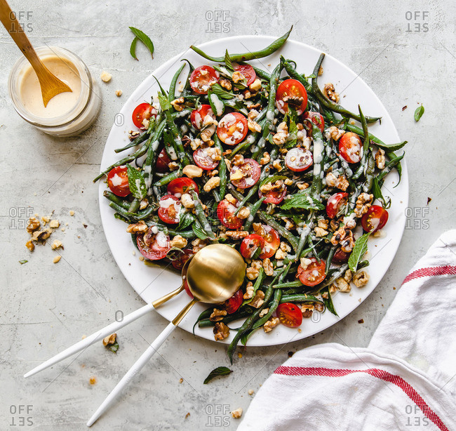summer green bean, cherry tomato and walnut salad on white plate and background