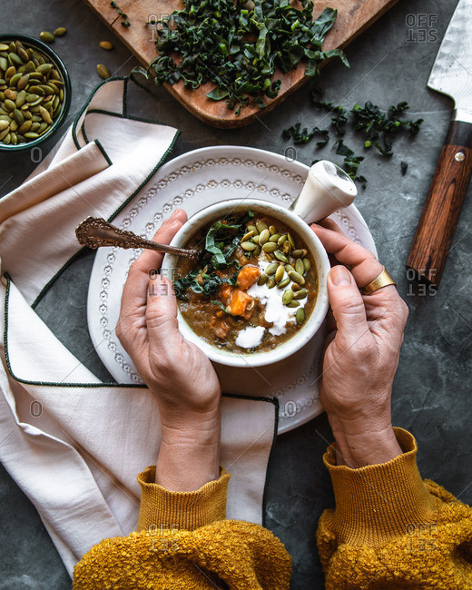 lentil, kale creamy soup garnished with carrots, pepitas, and cream, bowl held by two hands in a rustic setting, surrounded by ingredients cutting board and knife