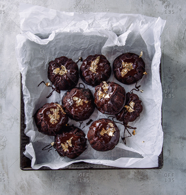 Mini flourless chocolate bundt cakes drizzled with melted chocolate, garnished with gold leaf and served in a vintage baking pan lined with parchment