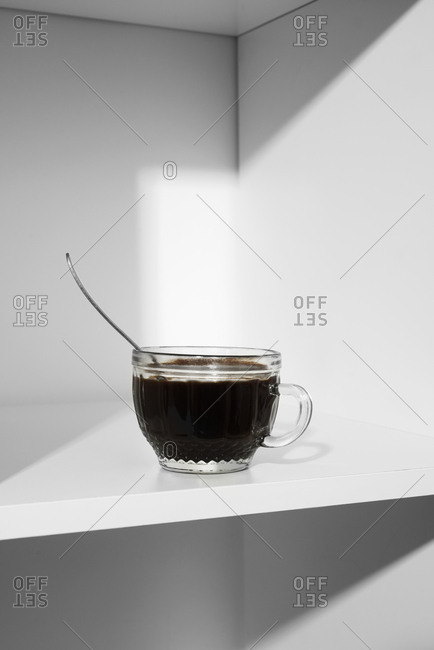 Close-up of a glass cup with coffee and a spoon on the shelves of a white bookshelf