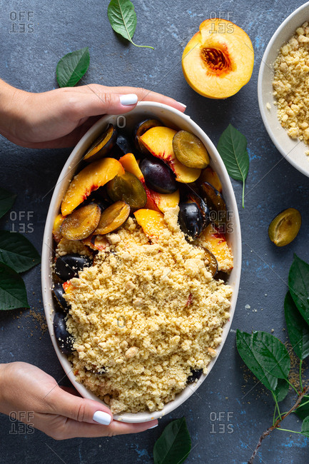 Female hands holding baking dish with peach plum pie