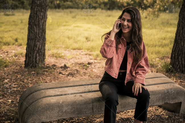 Portrait of a pretty brunette girl with a jacket sitting on a bench in nature while talking on a mobile phone