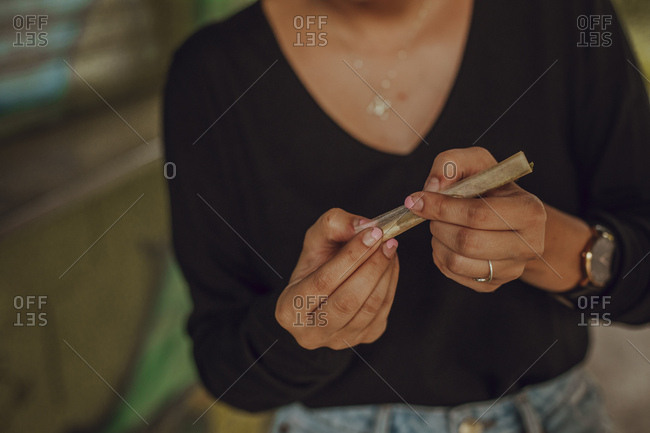 Close-up of a girl's hands preparing a marijuana joint