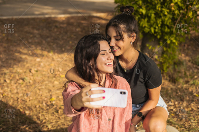 Two friends having fun smiling together while taking a selfie with their mobile phone