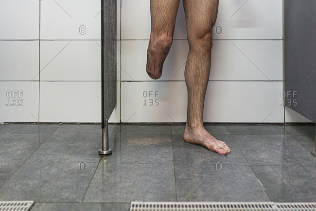 Unrecognizable athlete man and amputated one leg takes a shower after training