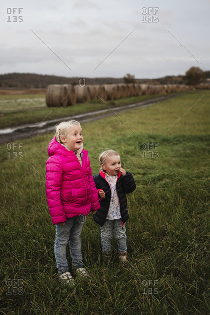 Two children holding hands on a field