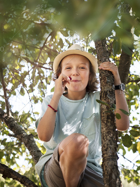 Girl eating cherries on tree
