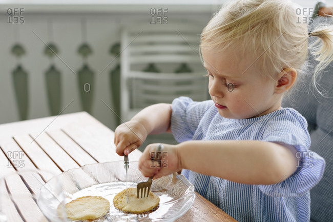 Girl eating cookie with fork and knife