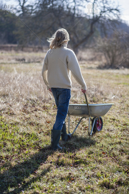 Woman pushing wheelbarrow