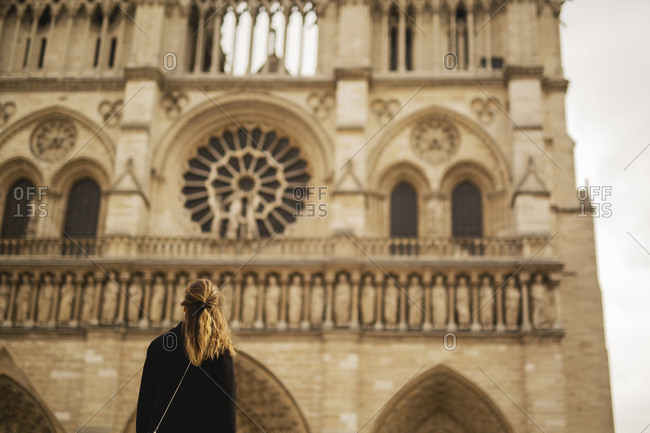 Woman looking at facade of Notre Dame de Paris, Paris, France