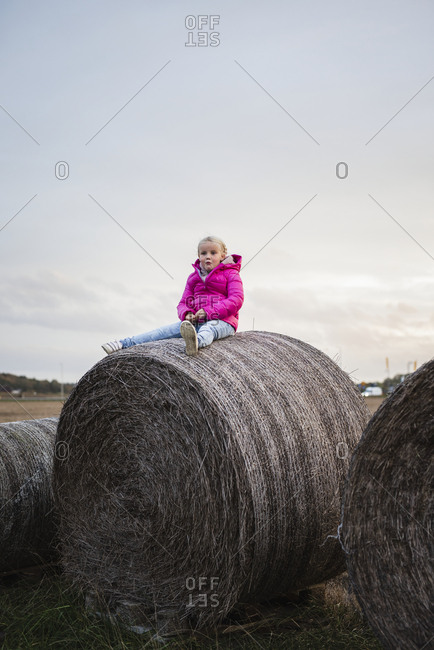 Girl sitting on bale of hay