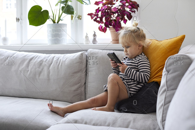 Girl on sofa using cell phone