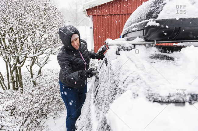 Woman clearing snow from car