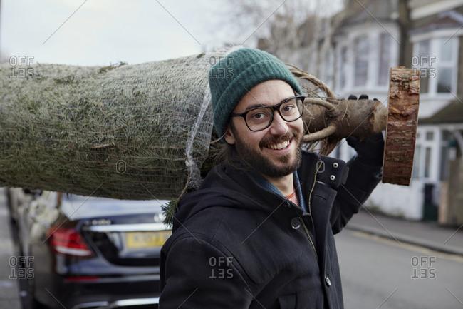 Smiling man carrying Christmas tree