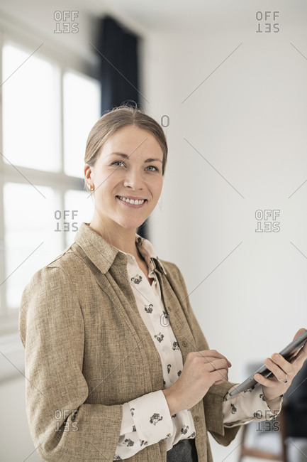 Businesswoman with cell phone looking at camera