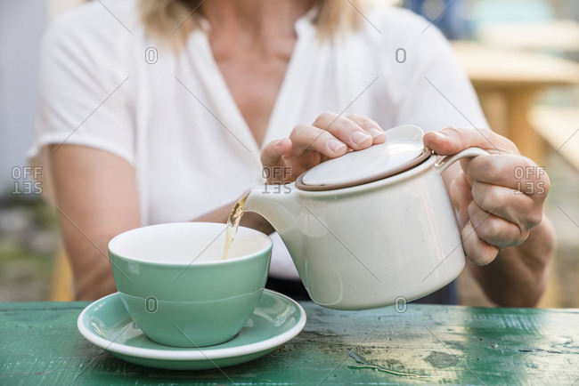 Woman pouring tea in to cup