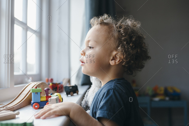 Young boy look outside window in his room