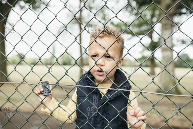 Young boy looks behind fence