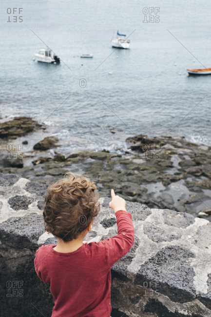 Boy looking over and pointing at boats in sea