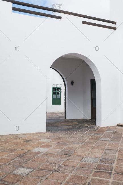 green window behind white wall archs