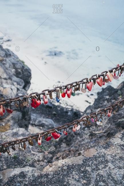 Love locks on chain above sea water in spain