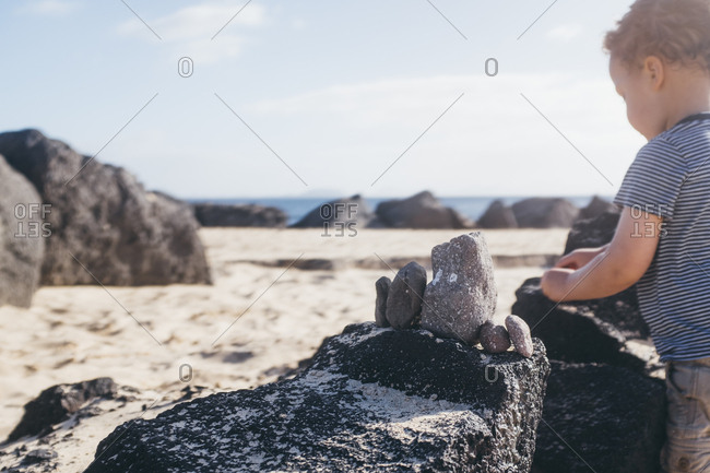 Young boy plays with rocks on beach