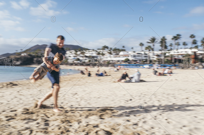 father and son plays on sandy beach in Lanzarote